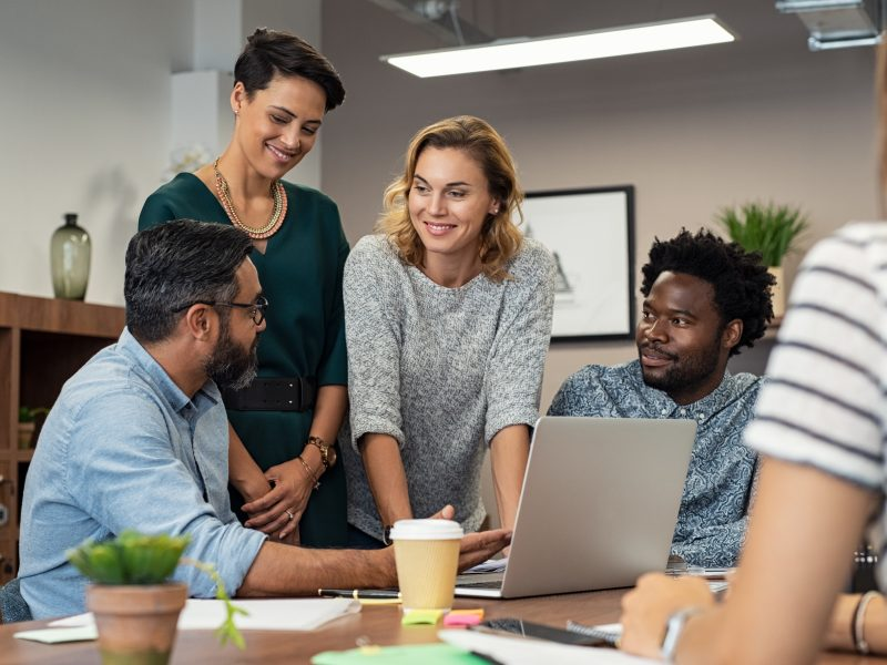 Multiethnic business people talking and smiling during meeting in office. Mature middle eastern man explaining proposal and planning with coworkers. Happy businessman showing project and marketing strategy on laptop to his colleagues.